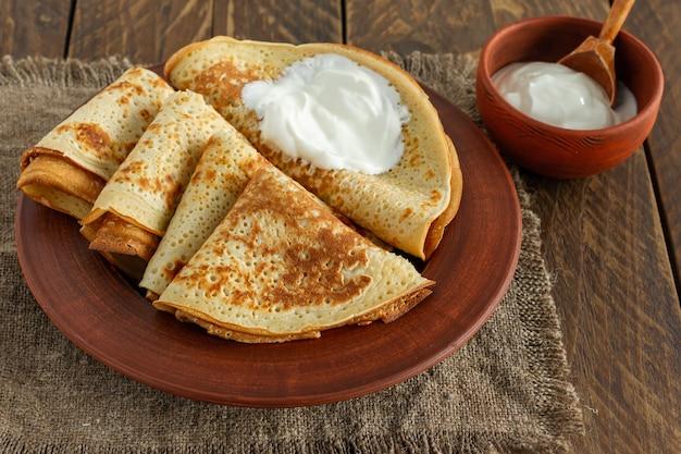 Стек блинов или блинов на тарелке, подается со сметаной. традиционная еда для русской масленичной недели. деревянный фон.
