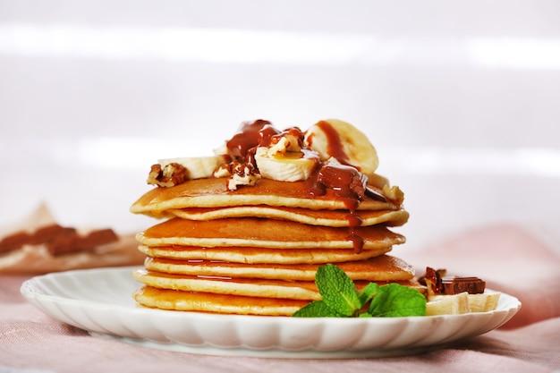 ミント、クルミ、チョコレート、バナナのスライスとパンケーキのスタックを布でテーブルに