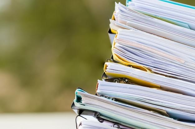 アーカイブの論文文書のスタックオフィスのテーブルのクリップ論文を含むファイル