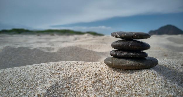 浜の砂の上の小石の山:内なる平和、静けさ、そして一般的な満足の禅の刺激的なイメージ。
