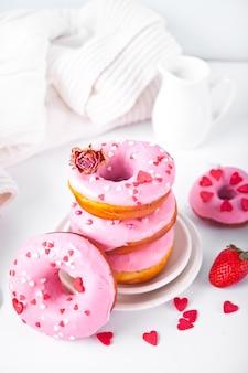 접시에 핑크 도넛의 스택입니다. 발렌타인 데이 개념.