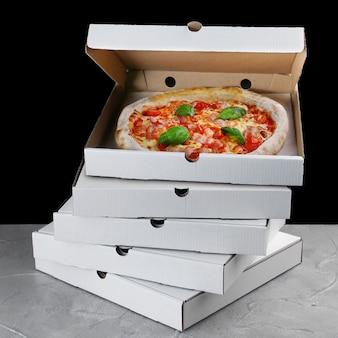 Стек коробки пиццы с пиццей внутри. доставка пиццы. коробка на черном столе. мясная пицца.