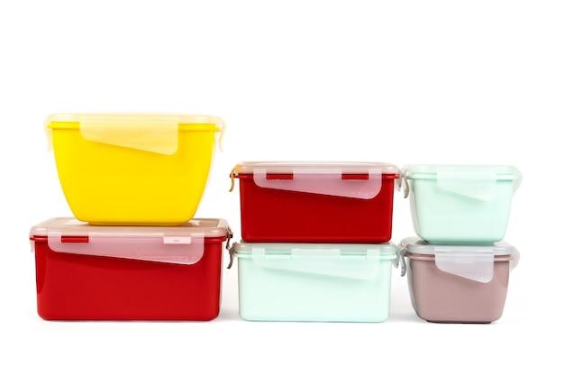 白い背景で隔離の食品用プラスチックマルチカラーコンテナのスタック。側面図