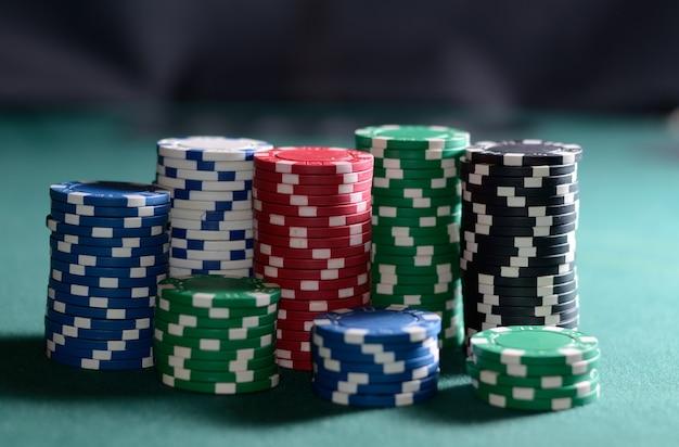 녹색 테이블에 포커 칩 스택입니다. 포커 게임 테마