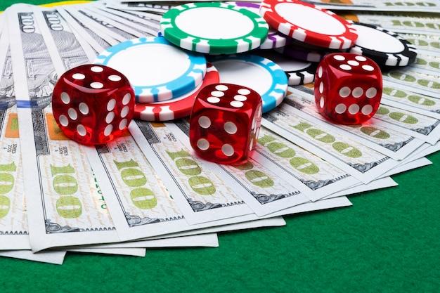 Стек фишек для покера с костями катится на долларовых купюрах. покерный стол в казино. игра в кости. игра в кости в казино.