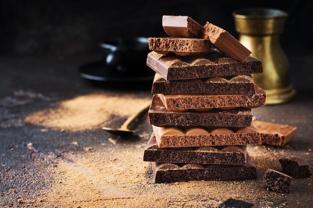 Стек пористого воздушного горького и молочного шоколада и какао на темном столе. ассорти из разных видов шоколада. выборочный фокус.