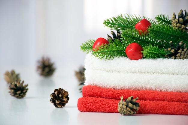 Стопка красных и белых полотенец с еловыми ветками, красными игрушками и сосновыми шишками на белом столе с окном из тюля
