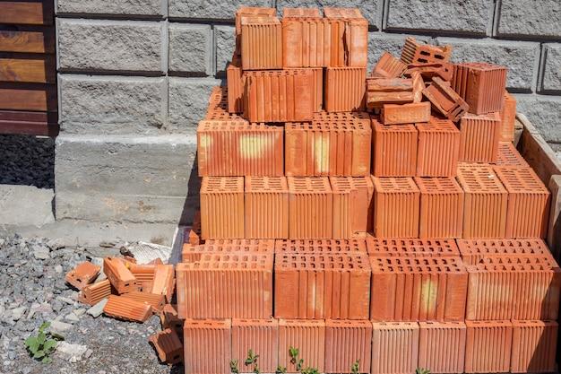 赤レンガのスタック:石積みレンガの壁の作業の詳細。