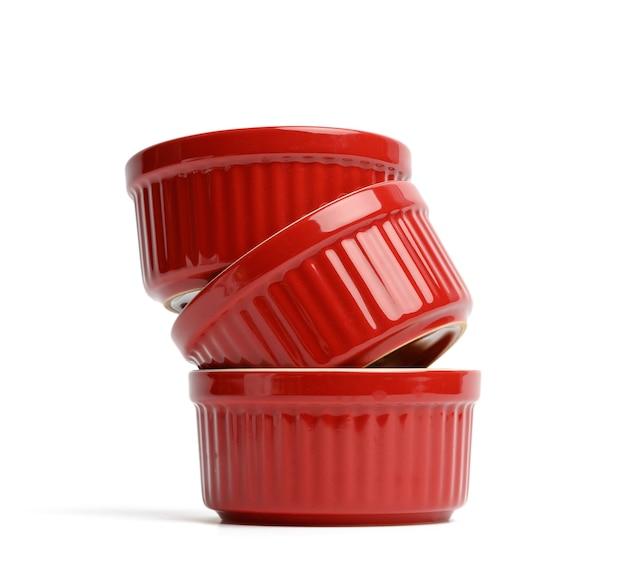 Стек красные керамические круглые формы для выпечки кексов, изолированные на белом фоне, крупным планом