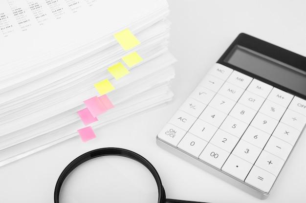虫眼鏡と計算機を使用したレポート財務データのスタック。ビジネス、金融、データ研究の概念。