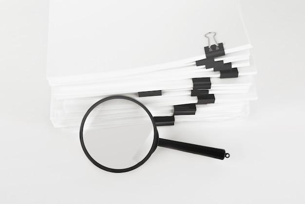 돋보기와 보고서 용지 문서의 스택입니다. 비즈니스 및 검색의 개념.