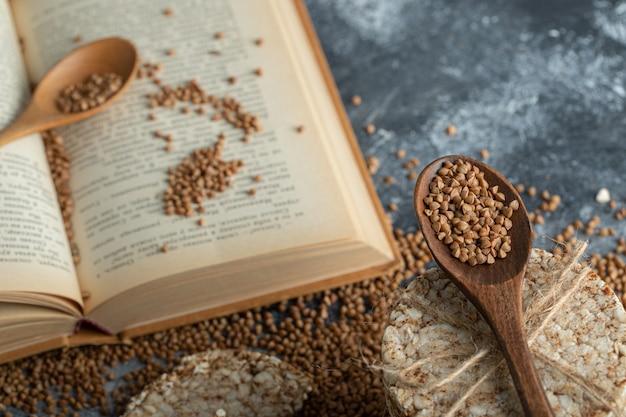Стопка рисовых лепешек, книги и сырой гречки на мраморной поверхности