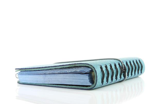 Стопка книги с переплетом или синей кожаной записной книжки на белом пространстве