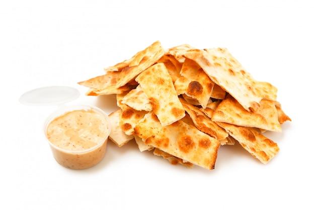 Стек соленых крекеров и соус внутри пластиковой упаковки