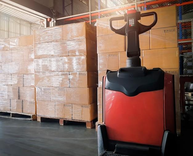 倉庫での出荷ボックスと電気フォークリフトパレットジャックのスタック。貨物の輸出入倉庫