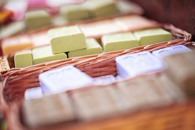 고리 버들 세공 바구니 안에 풍부한 비누 막대의 스택. 신선한 향이 나는 비누 바는 상점이나 창고의 바구니에 수집품을 쌓습니다. 바구니에 다른 향기를 가진 많은 비누 모음