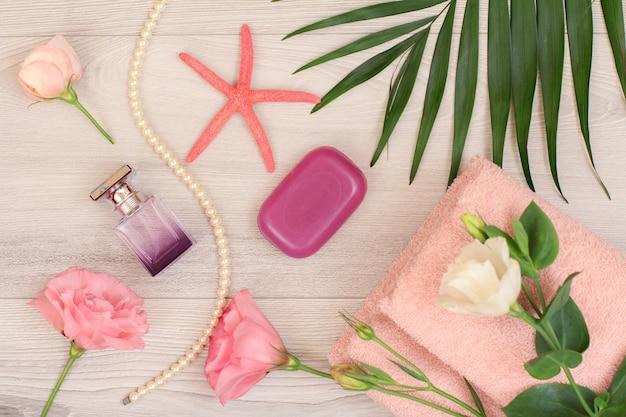 분홍색 꽃, 비누, 향수 한 병, 바다 별, 녹색 잎이 나무 배경에 있는 부드러운 테리 수건을 쌓으세요. 스파 제품. 평면도.
