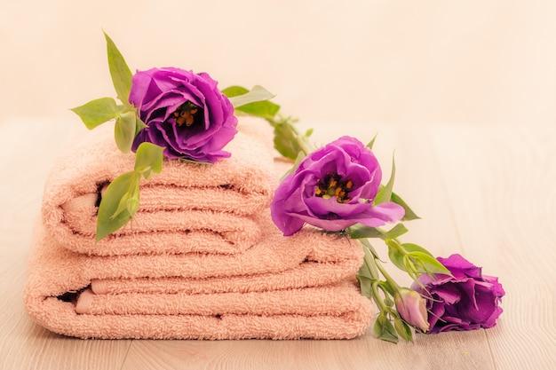 분홍색 배경에 보라색 꽃이 있는 부드러운 테리 수건 스택.