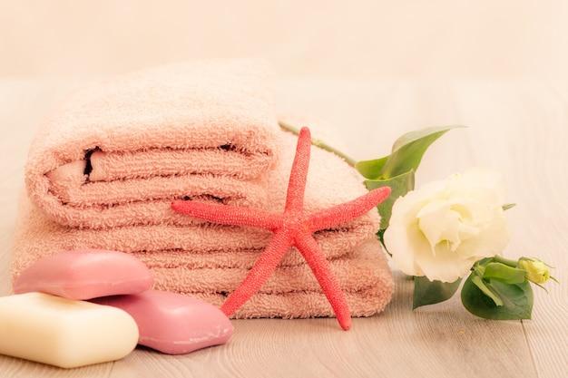 분홍색 배경에 흰 꽃, 비누, 바다별이 있는 부드러운 테리 수건을 쌓아라. 스파 제품.