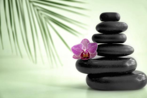 스파 돌과 밝은 배경에 아름다운 난초 꽃의 스택