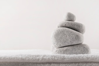 Stack of spa stones on soft folded towel against white background