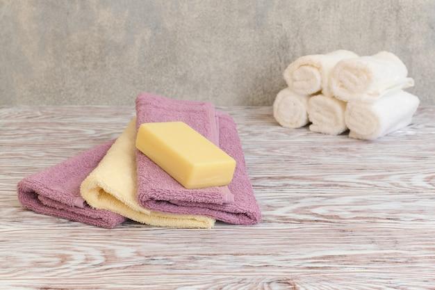 木製のテーブルにスパテリータオルと石鹸バーのスタック