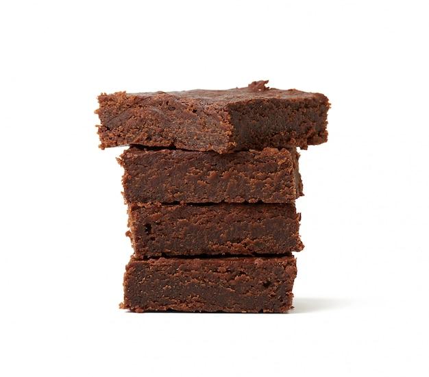 Стек квадратных выпеченных кусочков пирожного с шоколадным тортом, изолированных на белом