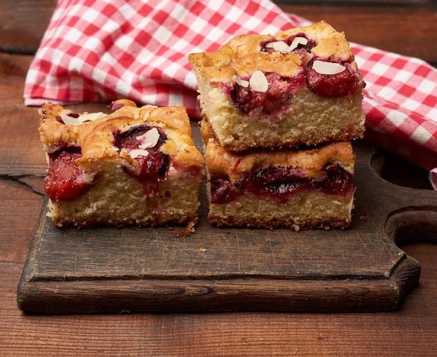 Стек квадратных запеченных ломтиков бисквита со сливами на деревянной кухонной доске
