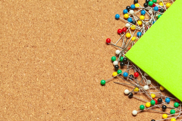 다채로운 푸시 핀의 무리로 둘러싸인 스티커 메모의 스택