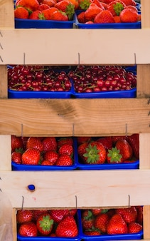 Stack of strawberries; cherries in the wooden shelf