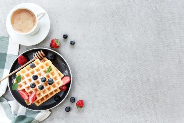 砂糖粉ワッフルと蜂蜜のスタックをタオルのプレートに置き、灰色のコンクリートまたはスレートのテーブルにブルーベリー、みじん切りのイチゴとミントの葉、白いカップとコーヒーのプレートを置く