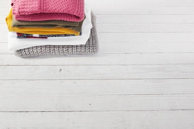 白い木製のテーブルにセーターのスタック