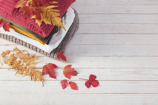 白い木製のテーブルに紅葉とセーターのスタック