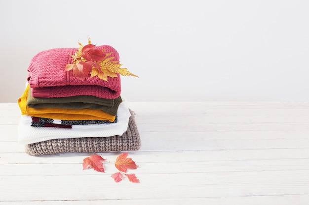 Стек свитера с осенними листьями на белом деревянном столе