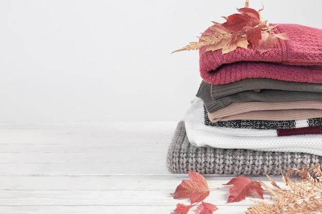 Стек свитеров с осенними листьями на белом деревянном столе
