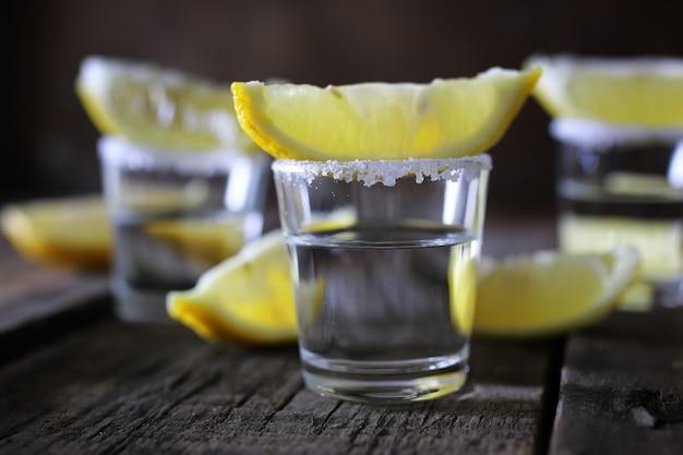 나무 배경에 소금과 레몬을 넣은 데킬라 스택