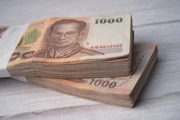 나무 배경에 태국 바트 지폐의 스택.