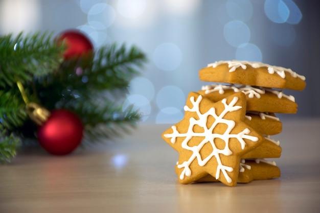 雪の結晶の形をした伝統的なクリスマスクッキーのジンジャーブレッドのスタック、白いアイシング、モミの枝、赤いおもちゃ、背景にボケライト