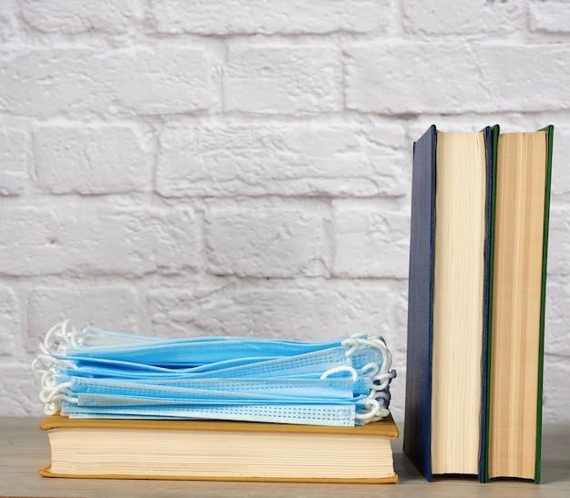 Стек различных книг и одноразовых медицинских масок