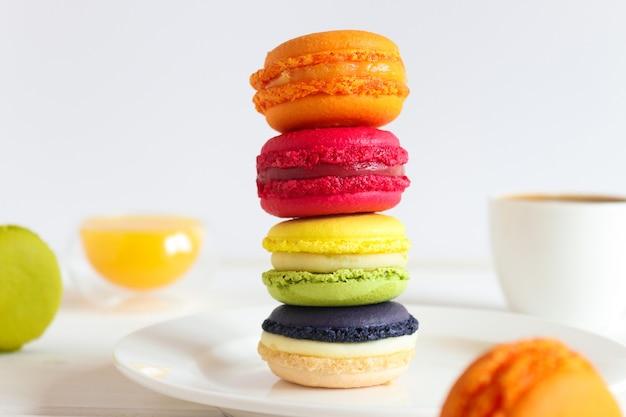 オレンジジュースとコーヒーのカップとテーブルの上のさまざまなカラフルなマカロンのスタックフランスのデザート
