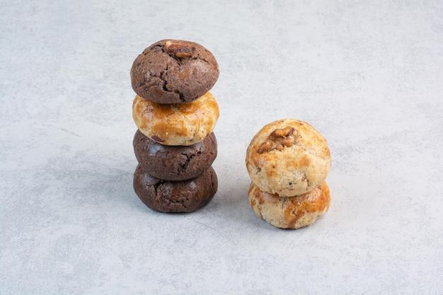 ベージュの背景にクルミとさまざまなクッキーのスタック。高品質の写真