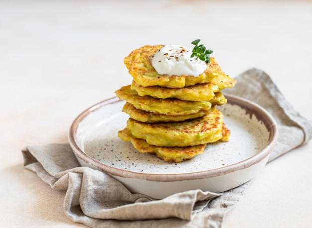 ヨーグルトまたはクリームサワードレッシングとハーブを添えた野菜のフリッターまたはパンケーキのスタック