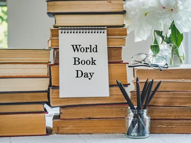 ヴィンテージ本のスタックと美しい花の花束。クローズアップ、孤立した背景。スタジオ写真。学習と教育の概念