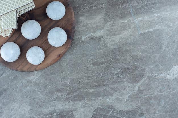 木の板に自家製の新鮮なクッキーとウエハースのスタック。