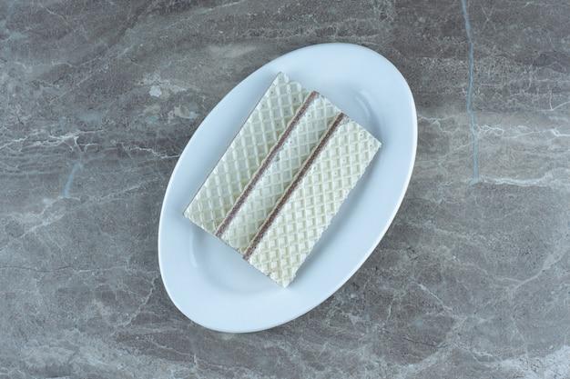 Стек вафель на белой тарелке над серым столом. вид сверху.