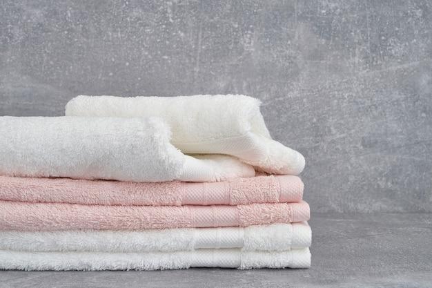 Стек белых и розовых банных полотенец на сером. копировать пространство