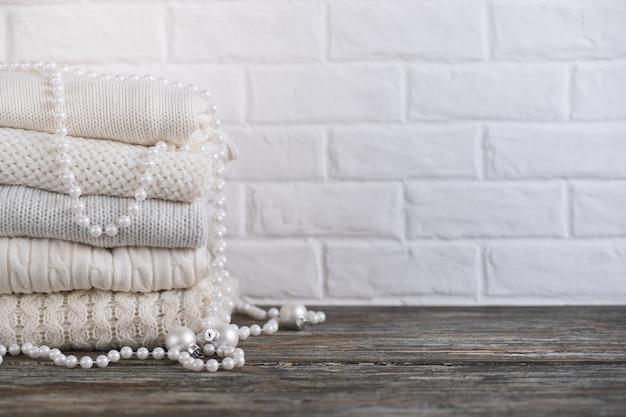 Стек белых уютных вязаных свитеров и бус на деревянном столе. место для текста.