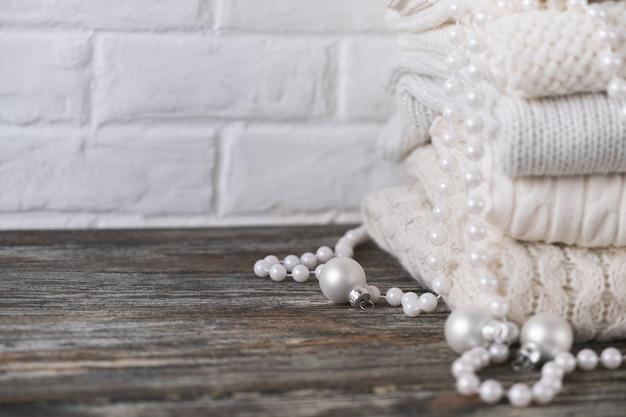 木製のテーブルに白い居心地の良いニットセーターのスタック