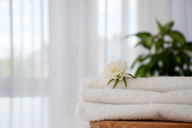 木の板に白い花と白い清潔なタオルのスタック。ランドリー、スパ、ドライクリーニングのコンセプト。コピースペース。