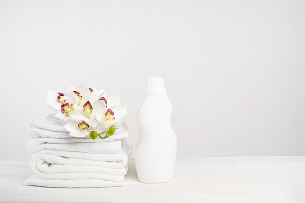 난초 꽃과 흰색 테이블에 흰색 리넨, 세척 젤 및 섬유 유연제의 스택. 복사 공간이있는 열대 호텔에서 모형 세탁의 날.